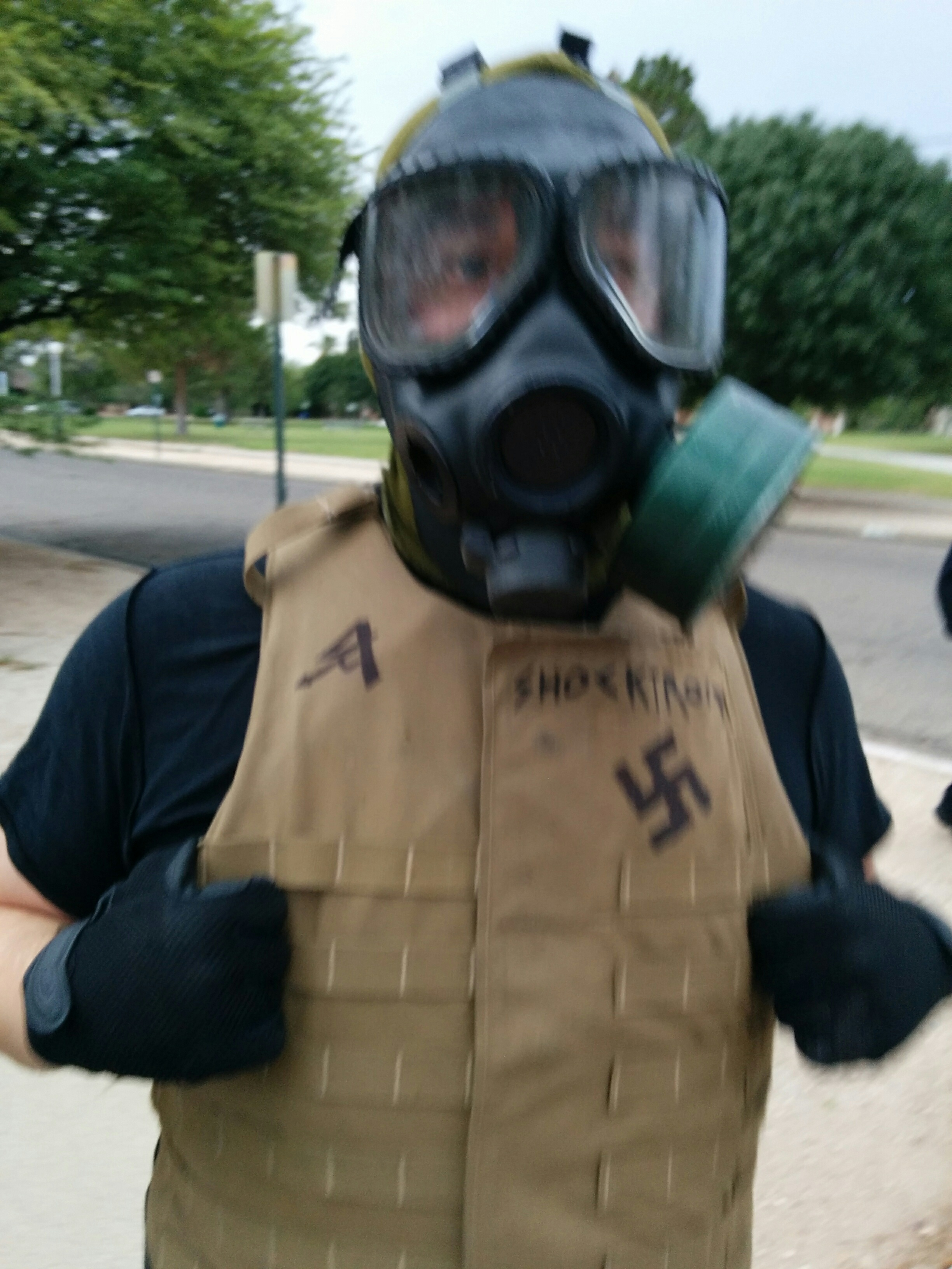 Close up of the Nazi in the gas mask, showing a swastika and the words I AM HATE sharpied on his flak jacket.